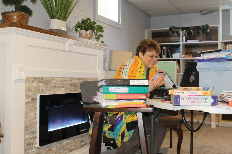 Professor Janet Weeda teaching pharmacology remotely in her workspace of her chilly basement.